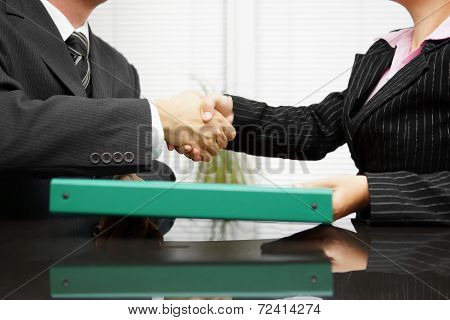 Businessman Is Passing Binder With Documentation  To His Client While Handshaking