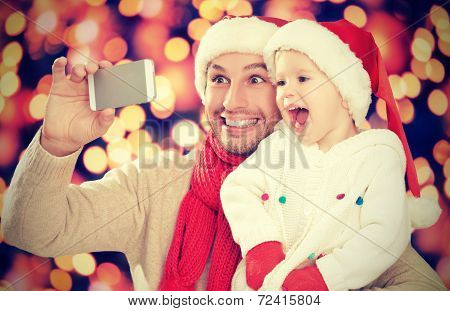 Selfe  In Christmas. Happy Family Dad Playing With Daughter And Photographed On  Mobile Phone