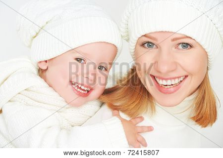 Happy Family On A Winter Walk. Mother And Baby Daughter In The White Hats