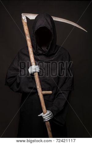 Death with scythe standing in the dark. Halloween.