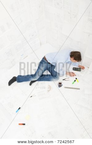 Engineer Surrounded By Technical Drawings
