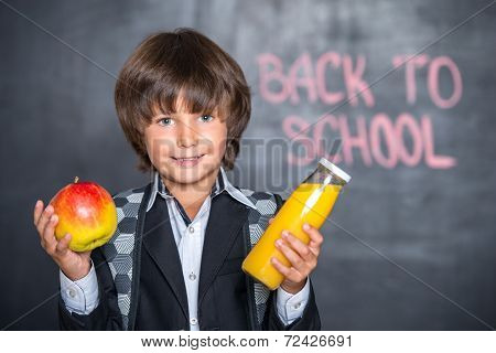 Close-up of little school boy with apple and juice near blackboa