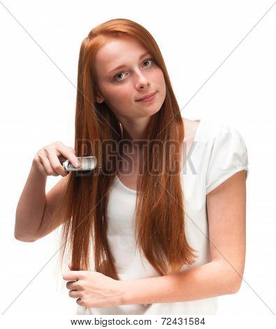 Young Red-haired Girl Combing Her Long Hair. Isolated On White Background