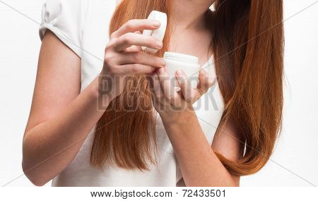 Young Red-haired Girl Holding A Package With A Face Cream. Isolated On White Background