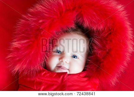 Cute Funny Baby Girl With Big Blue Eyes In A Warm Winter Jacket With Red Hood