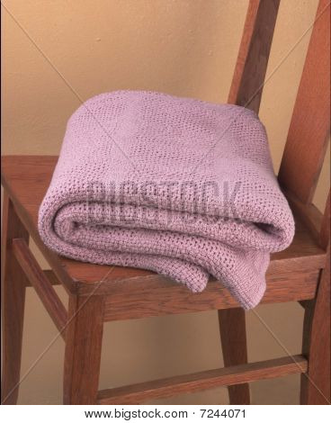 pink folded blanket on chair