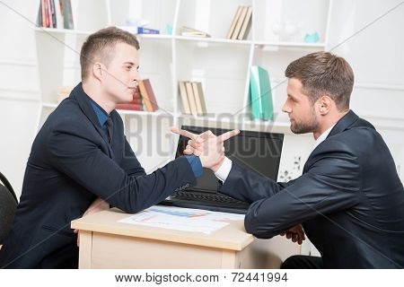 Waist-up portrait of two angry businessmen in suits sitting at t