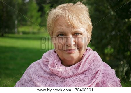 Portrait of happy pretty senior woman in the park on nature background