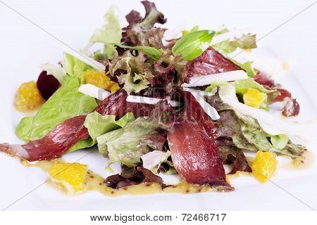 jerked beef, salad, lettuce, orange on the plate