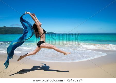 young woman jumping with waving blue cape scarf on tropical beach