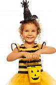 image of bucket  - Nice beautiful little girl with curly hair and bucket with candies standing isolated no white in Halloween hat with spider - JPG