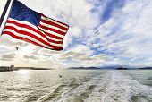 picture of alcatraz  - View of San Francisco Bay the Golden Gate bridge seagulls flying the american flag waving and Alcatraz island at sunset from a ferry in California United States - JPG