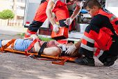 stock photo of accident victim  - Paramedics giving first aid girl after accident - JPG