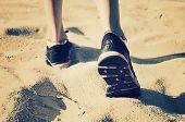 pic of girl walking away  - girl feet in sneakers go away on the sand - JPG