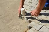 picture of laying-in-bed  - Worker laying pavers onto the bedding sand and fitting them into place - JPG