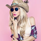 stock photo of redneck  - Sexy girl in cowboy fashion style on pink background - JPG
