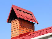 image of red roof tile  - Brick chimney on a red tiled roof taken closeup - JPG