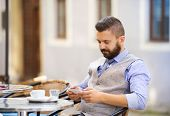 stock photo of lunch  - Modern hipster businessman drinking espresso coffee in the city cafe during lunch time and using mobile phone - JPG