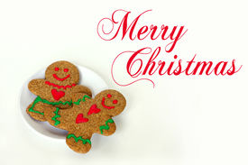 image of cursive  - A Christmas gingerbread man cookie with hearts on his shirt is laying on a white plate with a gingerbread woman on a white isolated background cursive text written Merry Christmas - JPG