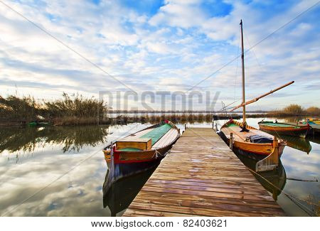 an old pier in the river with their traditional boats