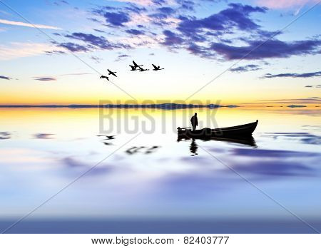 fisherman on wooden boat on the lake at sunrise