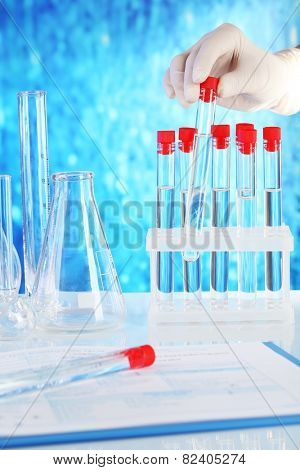 Hand holding test tubes and clipboard with medical history form on table on blue background