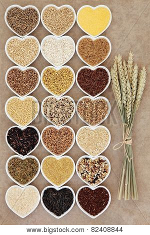 Grain and cereal food selection in heart shaped porcelain bowls over rough brown paper background with wheat ears.