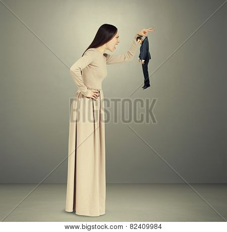 angry screaming woman in long dress holding small resentful man. photo in grey room