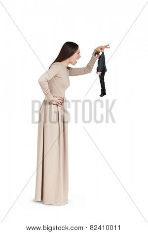 angry young woman holding small man and yelling at him. isolated on white ba?kground