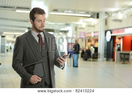 Young Businessman at the airport holding his phone and tablet