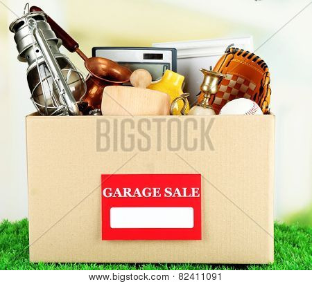 Box of unwanted stuff ready for a garage sale, on green grass