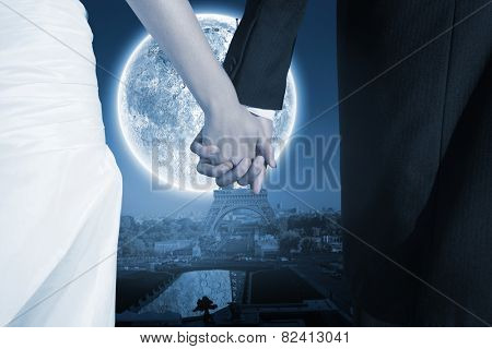 Close up of cute young newlyweds holding their hands against large moon over paris