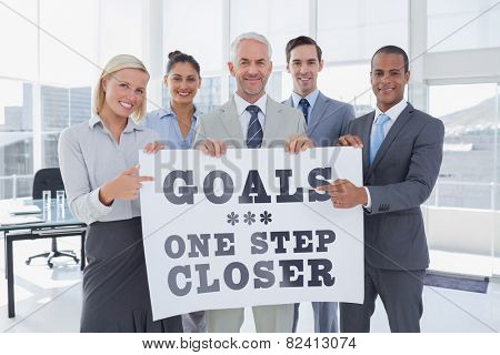 Business team holding large blank poster and pointing to it against goals one step closer