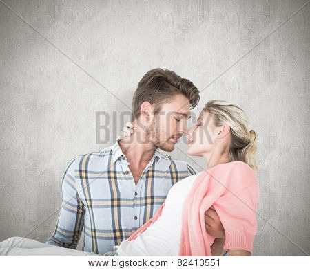 Handsome man picking up and hugging his girlfriend against white background