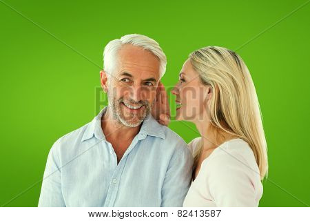 Woman whispering a secret to husband against green vignette
