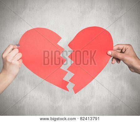 Two hands holding broken heart against weathered surface