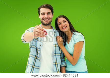 Happy young couple showing new house key against green vignette