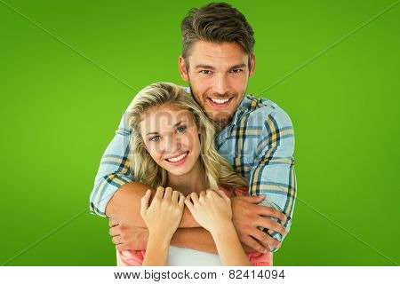Attractive young couple smiling at camera against green vignette