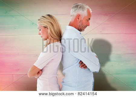 Unhappy couple not speaking to each other against pink and green planks