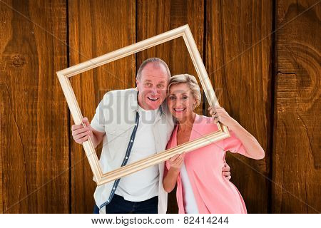 Older couple smiling at camera through picture frame against overhead of wooden planks
