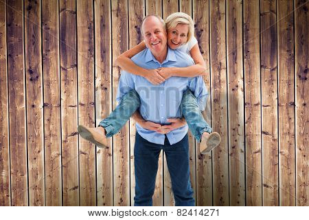 Mature man carrying his partner on his back against wooden planks background