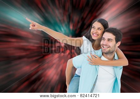 Happy casual man giving pretty girlfriend piggy back against digitally generated twinkling light design