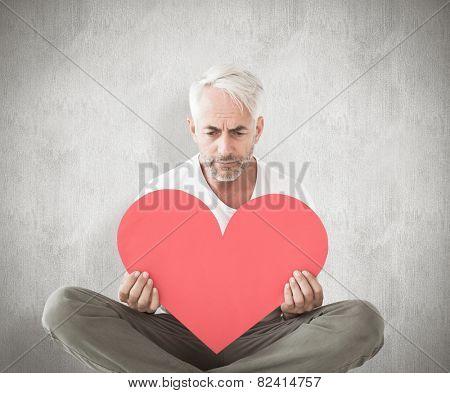 Upset man sitting holding heart shape against weathered surface