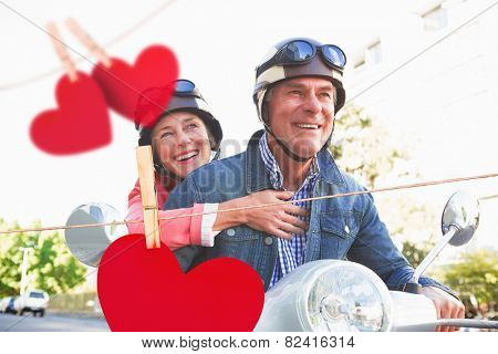 Happy senior couple riding a moped against hearts hanging on a line