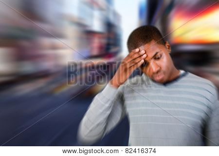 Man with headache against blurry new york street
