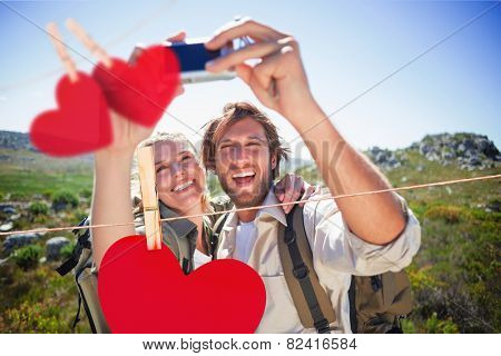 Hiking couple standing on mountain terrain taking a selfie against hearts hanging on a line