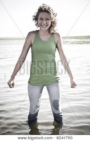 Smiling Blonde Standing in Water Fully Dressed