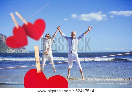 Happy couple jumping up barefoot on the beach against hearts hanging on a line