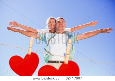 Happy senior man giving his partner a piggy back against hearts hanging on a line