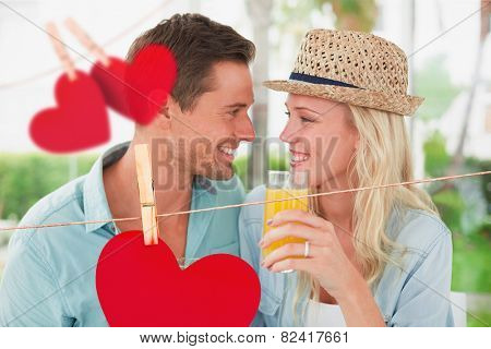Hip young couple drinking orange juice together against hearts hanging on a line